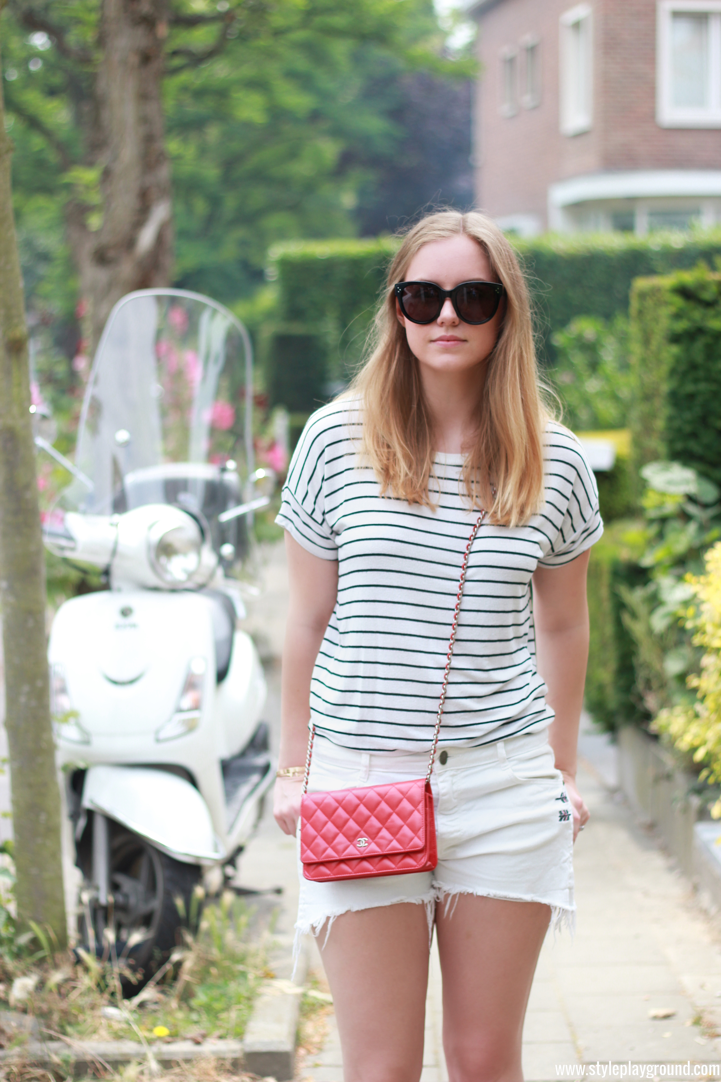 Axelle Blanpain from Style playground is wearing Zara shorts & t-shirt, white Converse sneakers, Chanel red WOC, Celine Audrey sunglasses