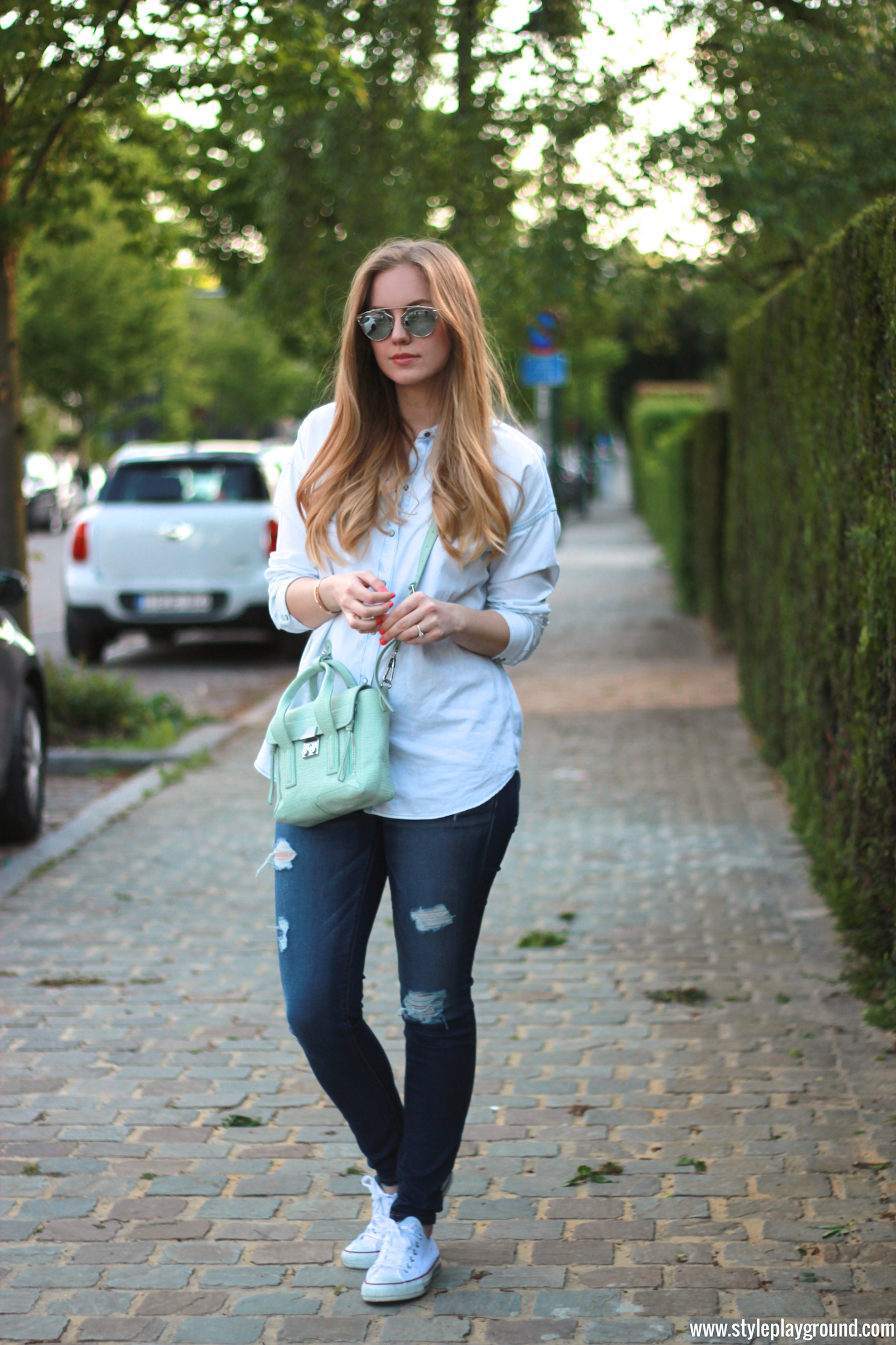 Axelle Blanpain of Style playground is wearing a Zara denim shirt, American Eagle ripped jeans, white Converse, Phillip Lim bag, Tiffany T bracelet and Cartier love bracelet